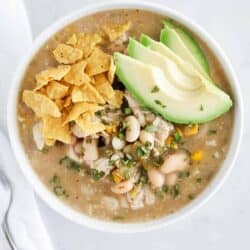 green enchilada chicken soup in bowl with avocado