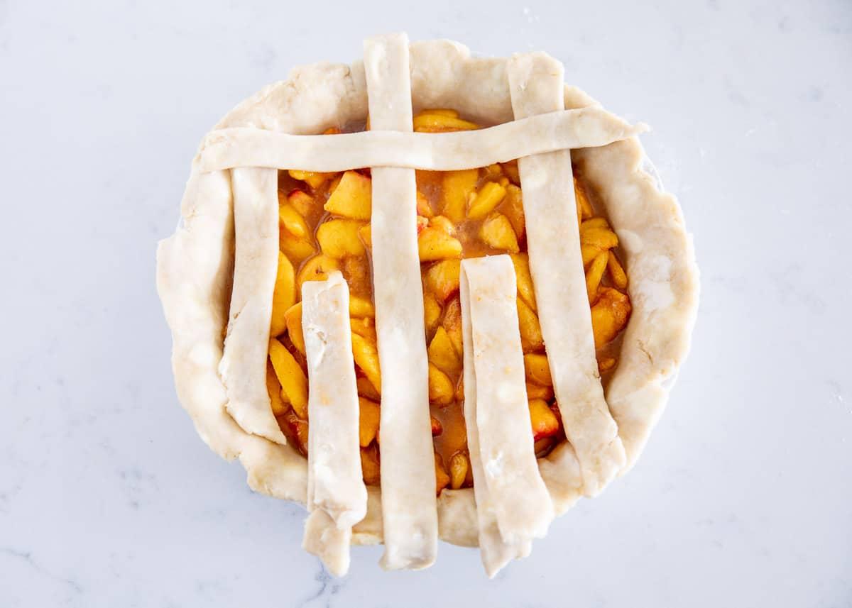 weaving pie crust on top of peach pie