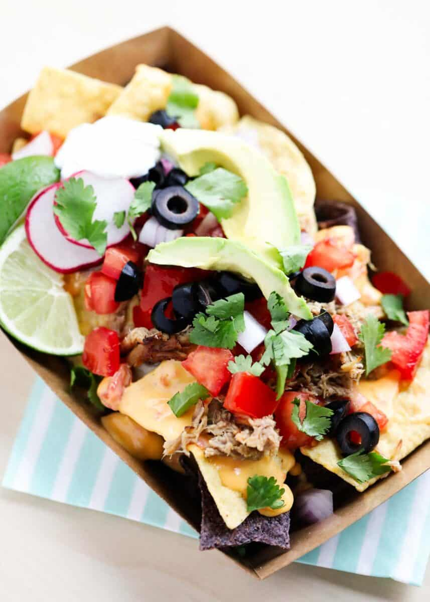nachos with toppings in cardboard container