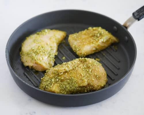 cooking pesto chicken in skillet