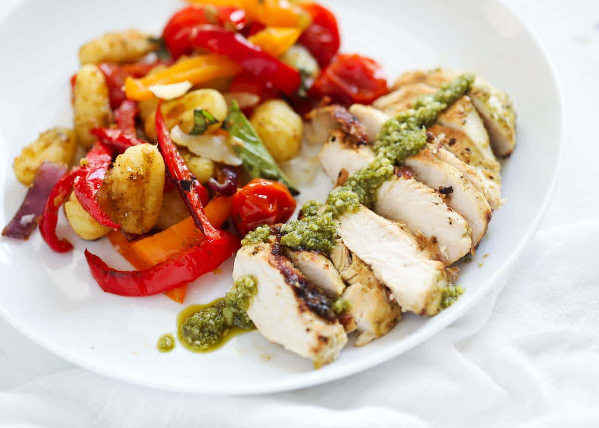 sliced pesto chicken on plate with vegetables
