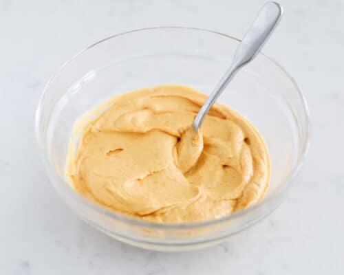 mixing pumpkin dip in glass bowl