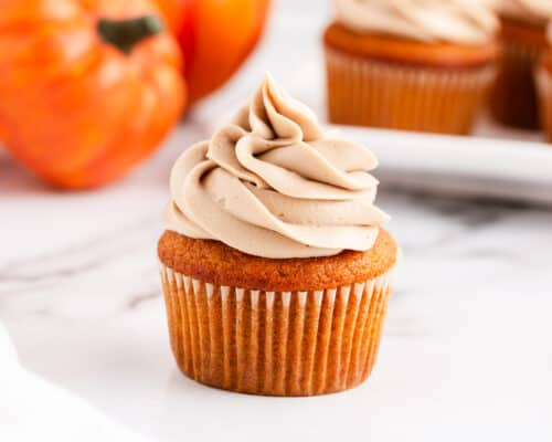 frosted pumpkin cupcake on counter