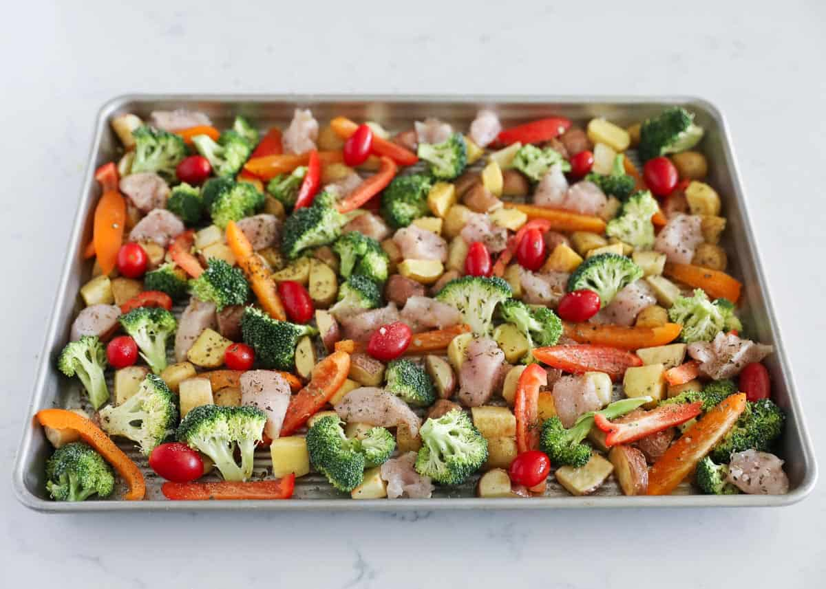 prepping chicken and vegetables on sheet pan