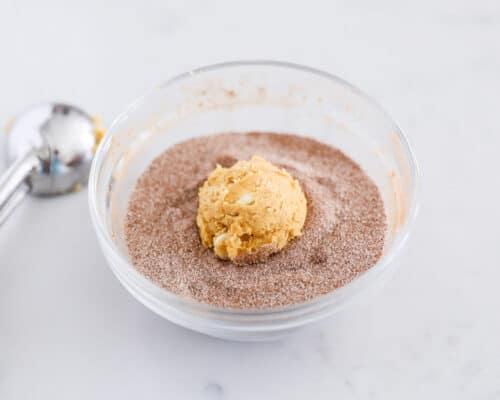 rolling cookie dough ball in cinnamon sugar