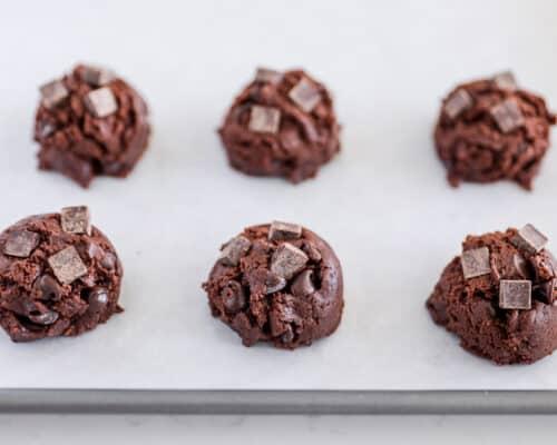 triple chocolate chunk cookie dough balls on pan