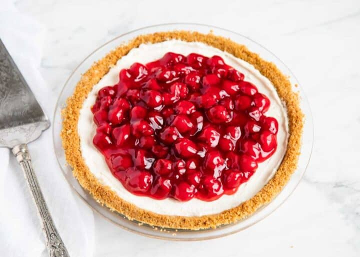 no bake cheesecake in pan with cherry filling on top