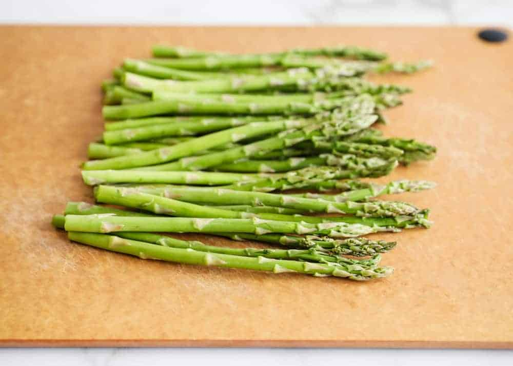 raw asparagus spears on a cutting board