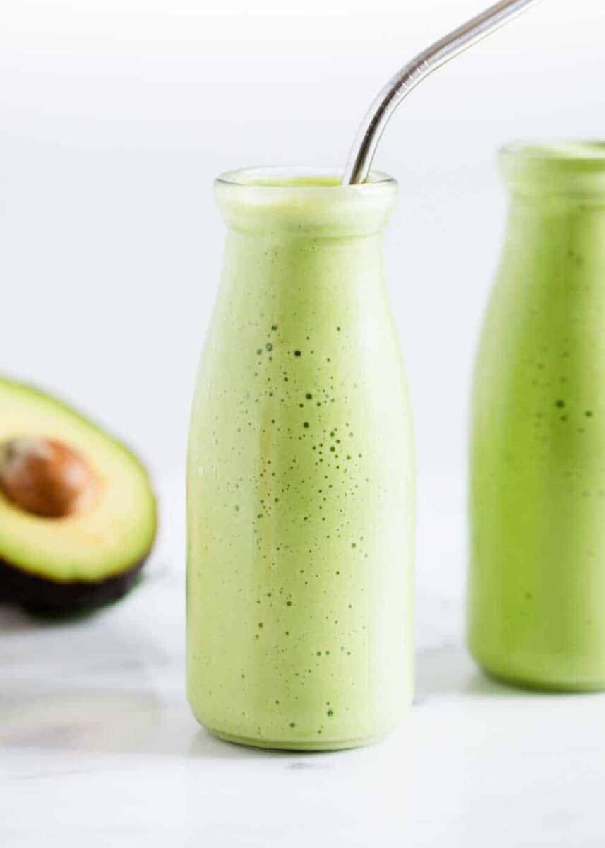 avocado smoothie in glass jar with straw