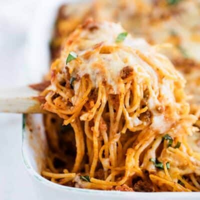 scooping baked spaghetti out of pan