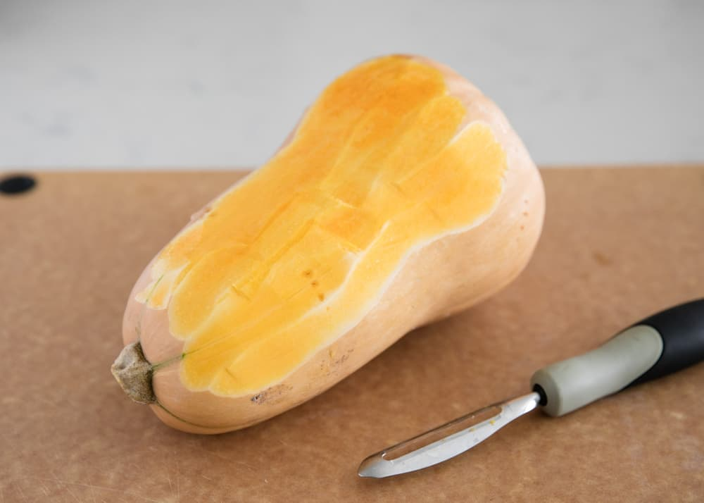 peeling a butternut squash with a potato peeler