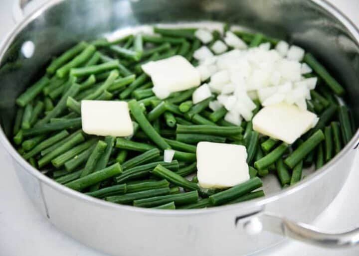 cooking green beans and onions in a skillet with butter